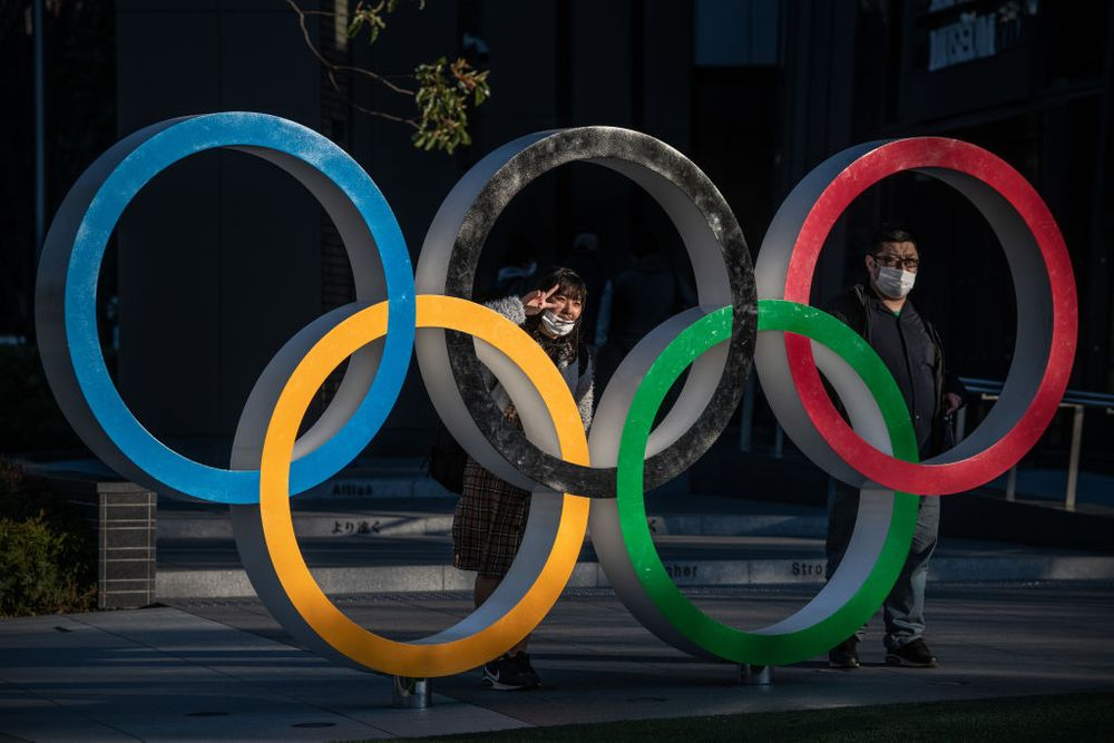 Two people standing behind human sized Olympic rings
