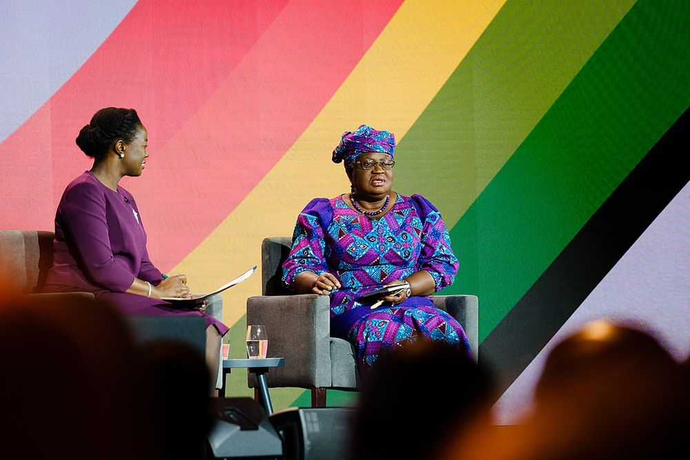 A photograph of Ngozi Okonjo-Iweala sitting on stage at the UK-Africa Investment Summit in front of a rainbow-striped background. She is wearing a colorful pink, purple, and turquoise dress and head wrap.