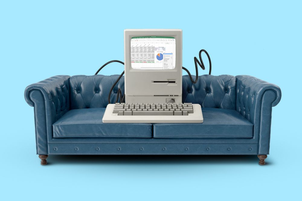 An illustration of an upholstered blue couch with an old computer and keyboard sitting on it.