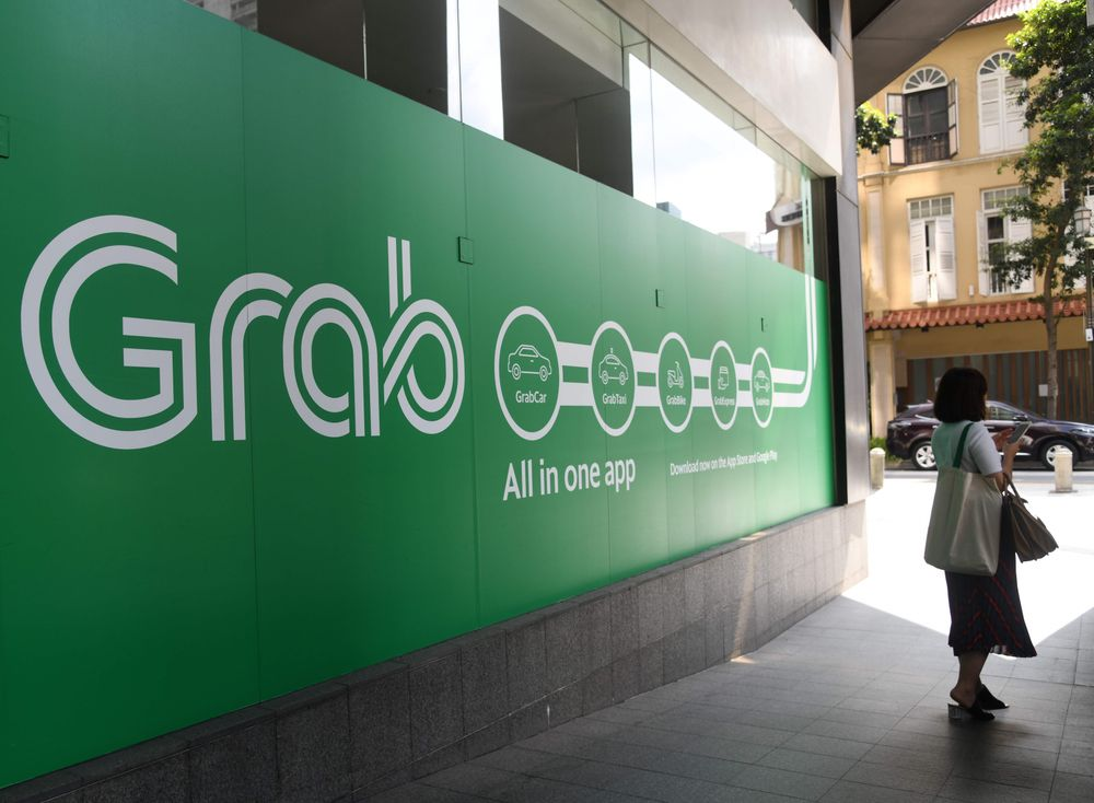 A woman stands outside the Grab transport office in Singapore on June 13...