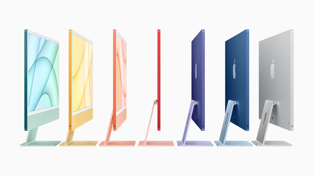 A photograph of seven Apple iMac computers in a line, photographed from the side. From left to right, the computers are turquoise, yellow, orange, red, purple, blue, and silver.
