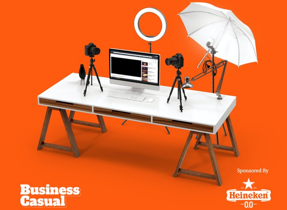 A photo of a white desk in front of an orange background. On the desk is a computer screen and keyboard, ring light, two tripods with a camera, and an umbrella reflector lighting kit.