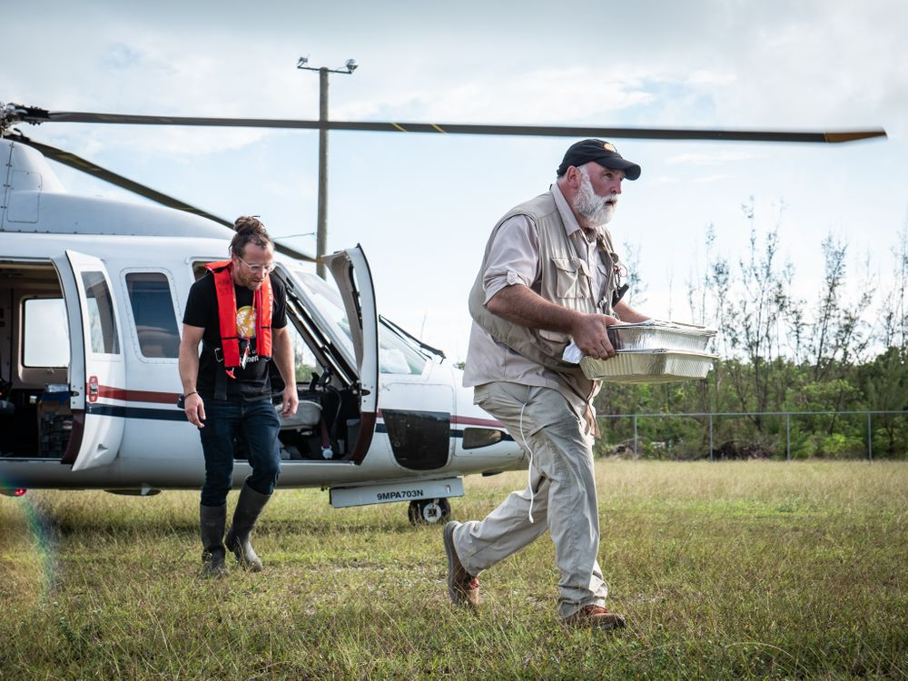 A photograph of chef Jose Andres walking away from a helicopter and carrying trays of food. He is wearing all-white and walking across a grass field.