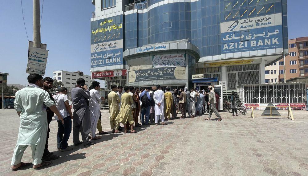 KABUL, AFGHANISTAN 15: Afghan people line up outside AZIZI Bank to take ...