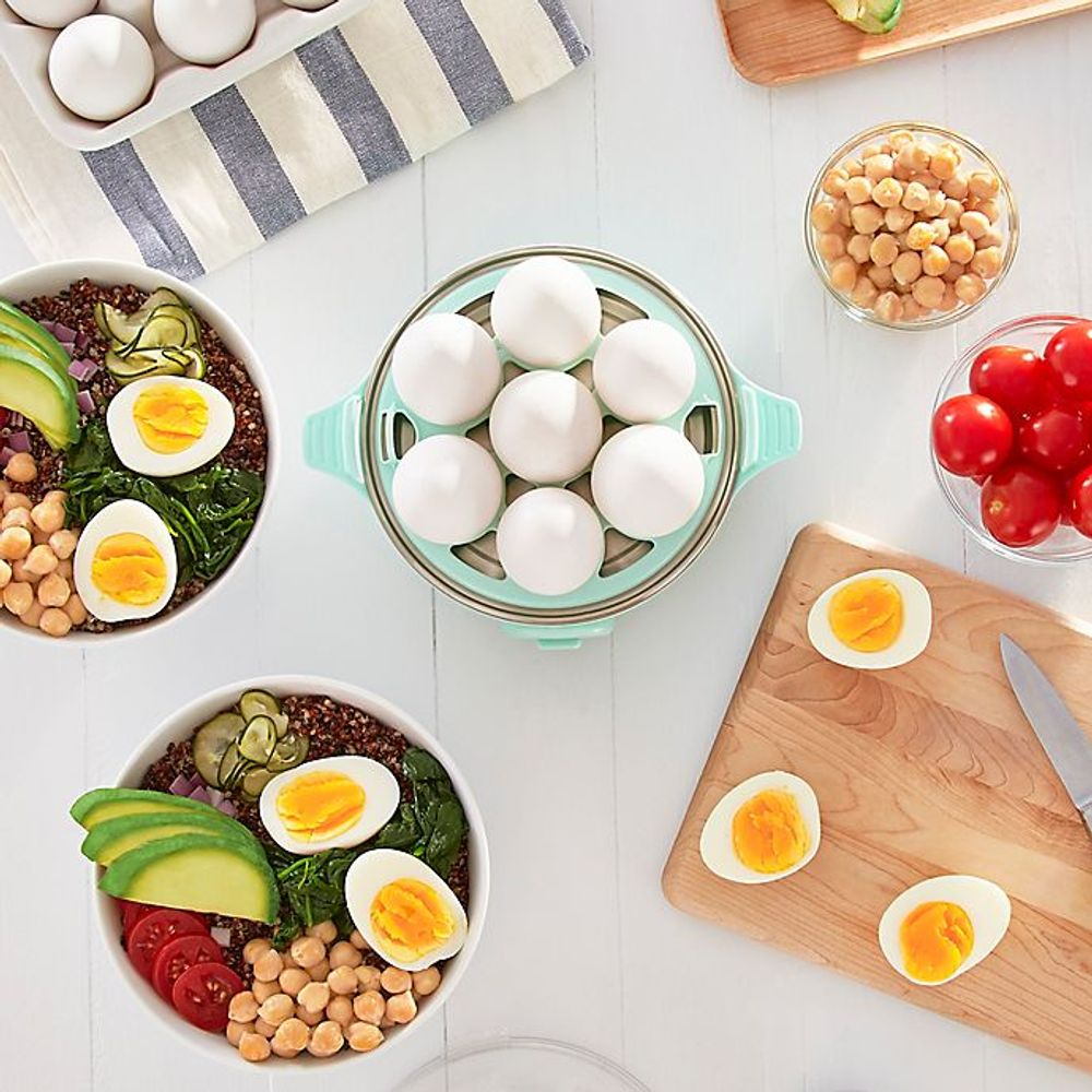 Egg Cooker on counter with deviled eggs on cutting board and in bowls