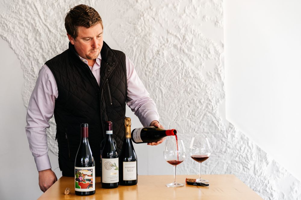 Ian Cauble, Master Sommelier pours wine into a glass