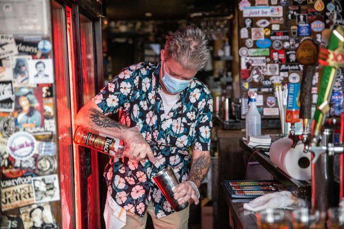 Florida masked bartender pouring a drink
