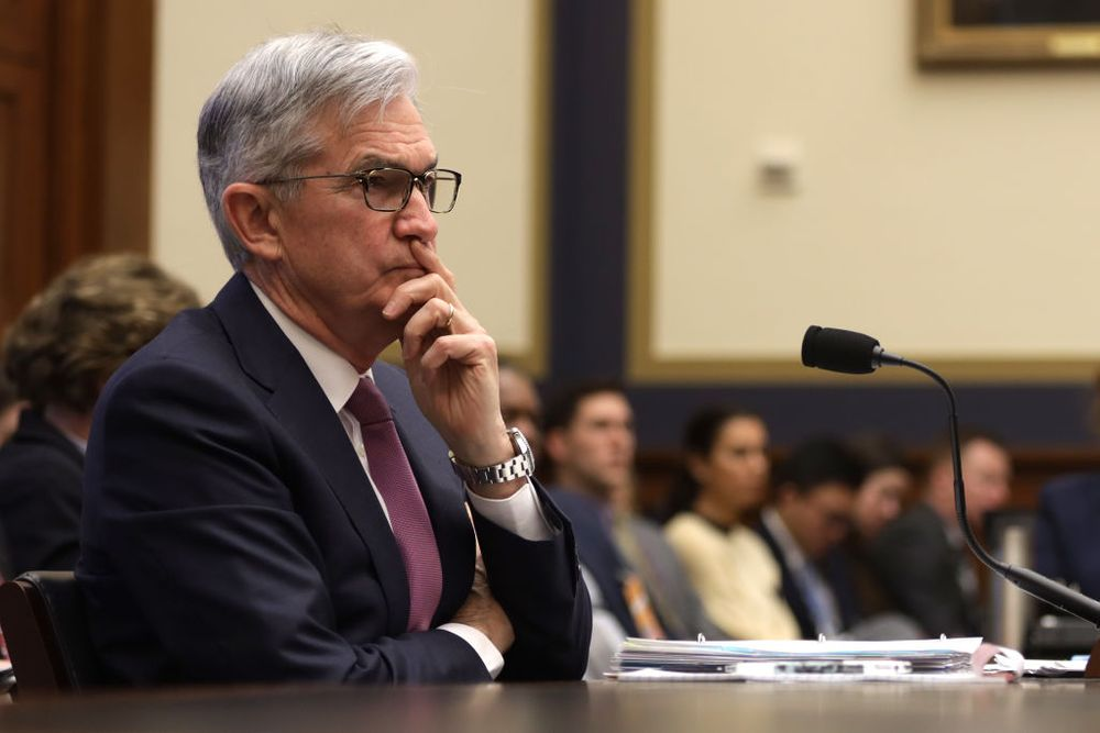 Jerome Powell sitting at a desk looking concerned