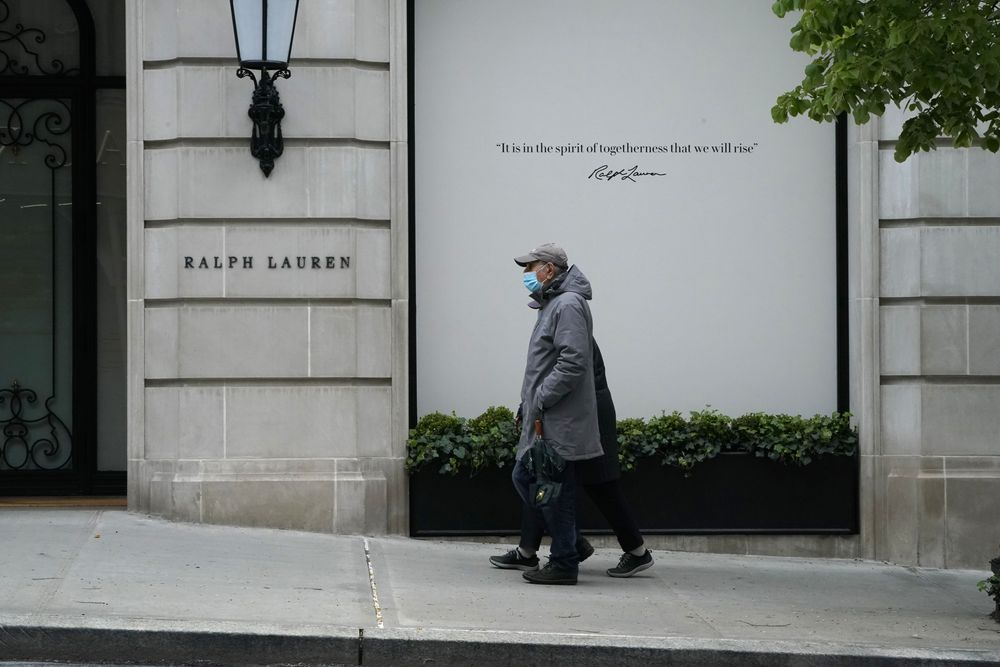 A couple walk past a boarded up Ralph Lauren store on Madison Avenue in ...