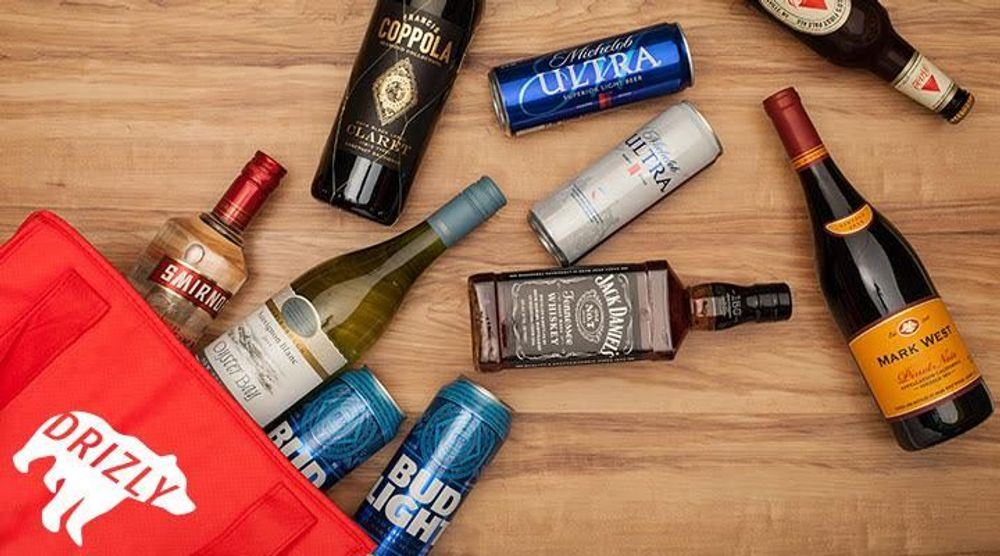 """A photograph of a red bag with the Drizly logo (a white bear with the word """"Drizly"""" in it"""" on a wooden table; spilling out of the bar are various bottles of wine, beer, and liquor"""